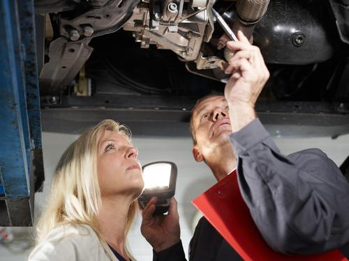 Automechaniker und Frau unter dem Auto