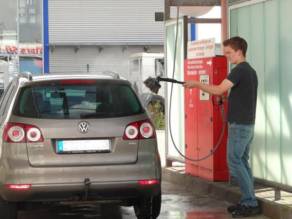 Junger Mann wäscht Auto